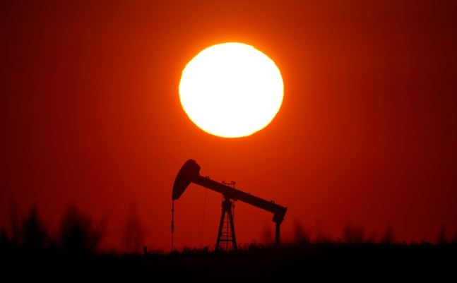The sun sets behind an oil pump outside Saint-Fiacre, near Paris, France.