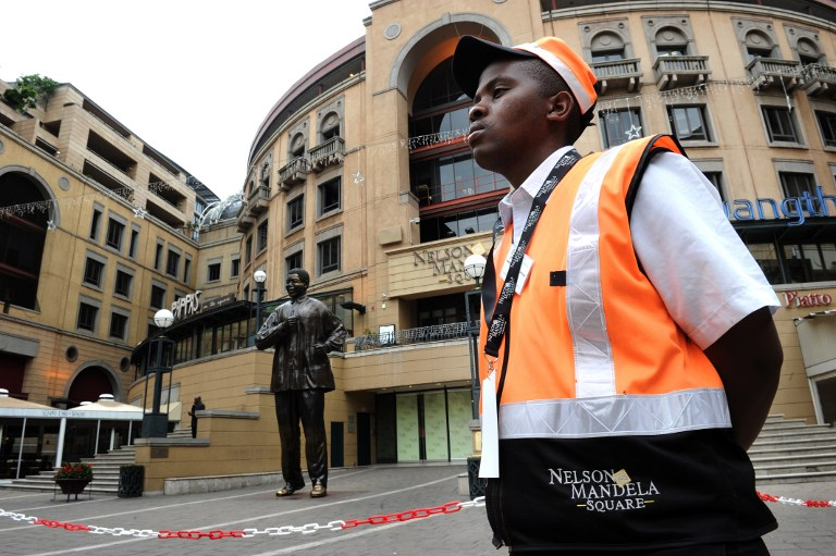 A security member stands guard on December 6, 2013 in front of a statue of former President Nelson Mandela