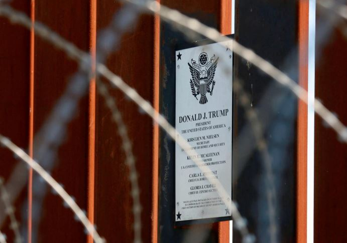 A plaque commemorating U.S. President Donald Trump hangs on the U.S.-Mexico border fence as Trump visits the U.S.-Mexico border in Calexico, California.