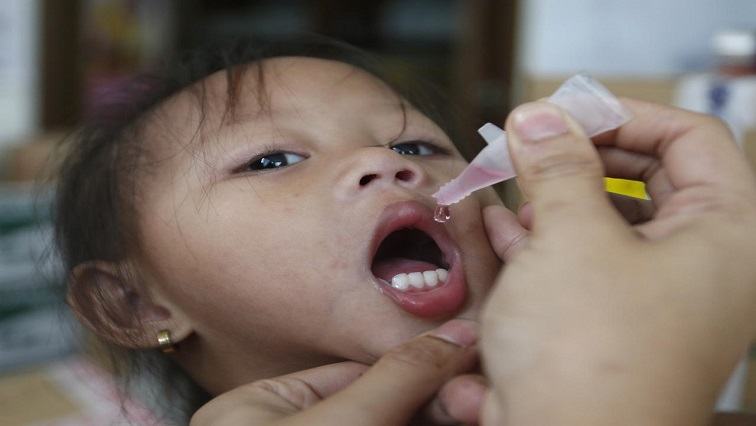 A girl receives anti-measles vaccination drops
