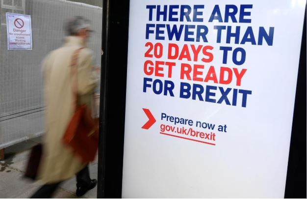 A man walks past an UK government Brexit information campaign poster at a bus stop in central London.