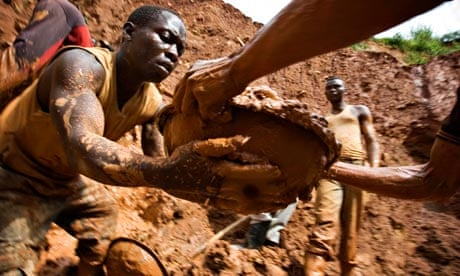 Congo mine collapse – workers form a human chain while digging an open pit in Kilomoto, north-east of the country.