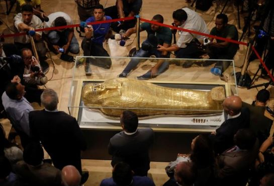 The Gold Coffin of Nedjemankh surrounded by members of media during a news conference to announce its return from the US and display at the National Museum of Egyptian Civilization.