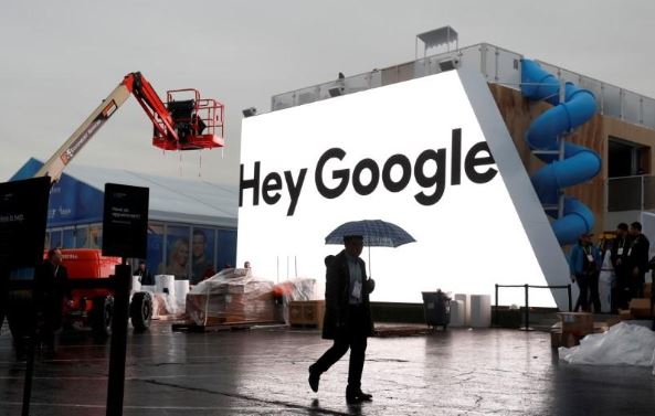 A man walks through light rain in front of the Hey Google booth under construction at the Las Vegas Convention Center in preparation for the 2018 CES in Las Vegas.