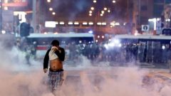 A man runs among the tear gas during a protest in Hong Kong, China.