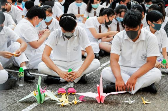 Schoolmates of a student protester who was shot by a policeman on Tuesday sit beside paper cranes while participating in a student gathering at Tsuen Wan Public Ho Chuen Yiu Memorial College in solidarity with the student in Tsuen Wan.