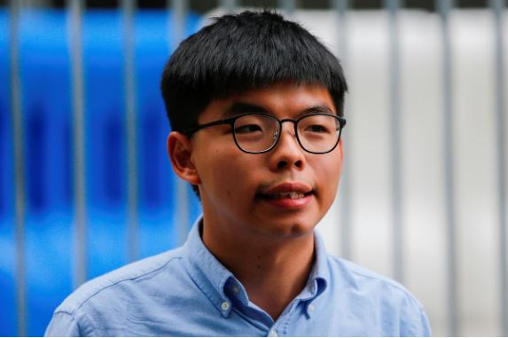 Pro-democracy activist Joshua Wong speaks to journalists after being disqualified from running in local district's council elections in November.