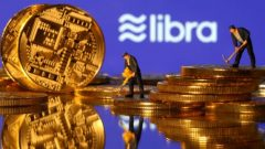 Small toy figures are seen on representations of virtual currency in front of the Libra logo in this illustration picture.