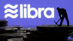 A small toy figure stands on representations of virtual currency in front of the Libra logo in this illustration picture.