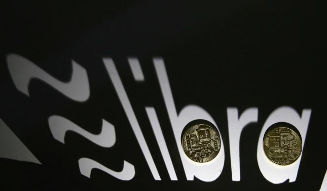 Shadow of a 3D-printed Facebook Libra cryptocurrency logo is seen near cryptocurrency representation.