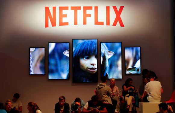 Gamers and visitors take a rest at the booth of Netflix during Europe's leading digital games fair Gamescom.