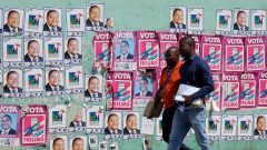 Mozambicans walk past election posters ahead Tuesday's provincial and legislative election.