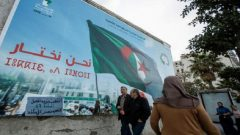 People walk past a campaign poster for presidential election in Algiers, Algeria.