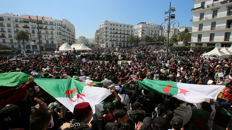 People take part in a protest demanding immediate political change in Algiers, Algeria.