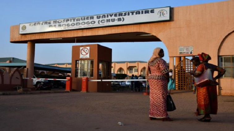 Women stand outside Bogodogo hospital where officials met with family members of victims of an ambush on workers near a Canadian-owned mine, in Ouagadougou, Burkina Faso.