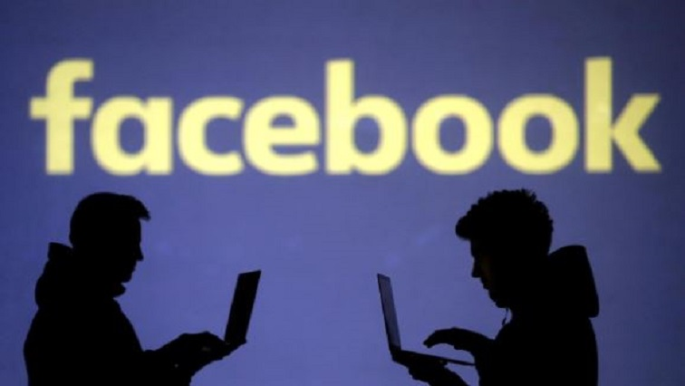 Silhouettes of laptop users are seen next to a screen projection of Facebook logo in this picture illustration.