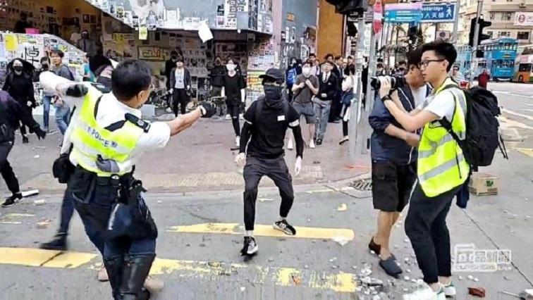 A still image from a social media video shows a police officer aiming his gun at a protester in Sai Wan Ho, Hong Kong.