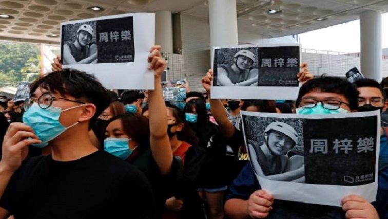 Students hold images of Chow Tsz-Lok, 22, a university student who fell during protests at the weekend and died early on Friday morning, during a ceremony to pay tribute to him at the Hong Kong University.