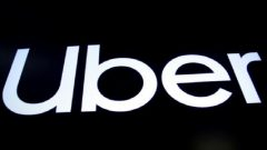 A screen displays the company logo for Uber Technologies Inc. on the day of it's IPO at the New York Stock Exchange.
