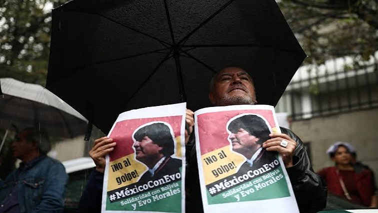 A man holds a sign during a demonstration in support of Bolivian President Evo Morales after he announced his resignation
