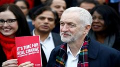 Britain's opposition Labour Party leader Jeremy Corbyn poses with his party's manifesto as he visits Labour activists.