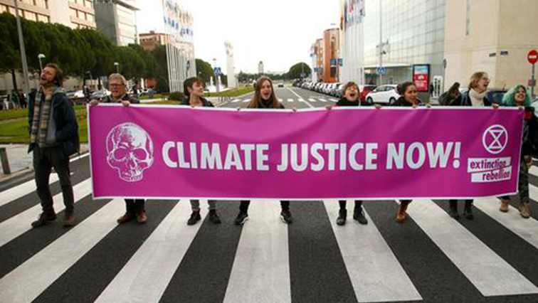Activists hold a banner during a protest against climate change as the COP25 climate summit is held in Madrid.