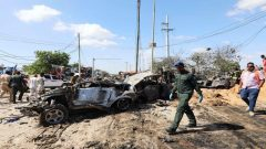 A Somali police officer walks past a wreckage at the scene of a car bomb explosion at a checkpoint in Mogadishu.