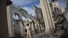 A woman prays among the rubble of the damaged main cathedral in downtown Port-au-Prince.