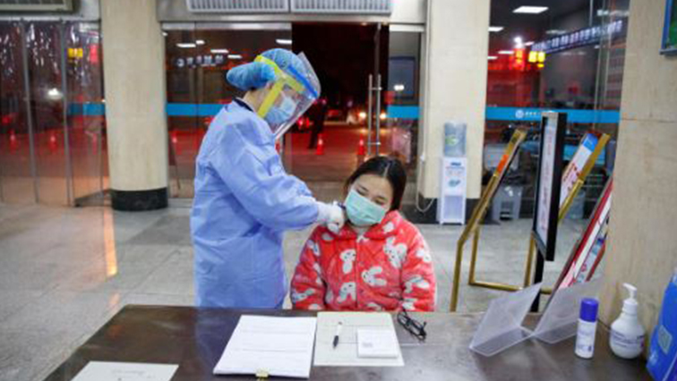 A nurse takes the temperature of a woman in the reception area of the First People's Hospital in Yueyang, Hunan Province, near the border to Hubei Province, which is under partial lockdown after an outbreak of a new coronavirus, in China.