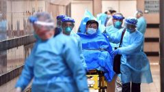 Medical staff transfer a patient of a highly suspected case of a new coronavirus at the Queen Elizabeth Hospital in Hong Kong, China.