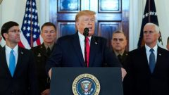 U.S. President Donald Trump delivers a statement about Iran flanked.
