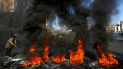 A man burns tires during ongoing anti-government protests in Najaf , Iraq.