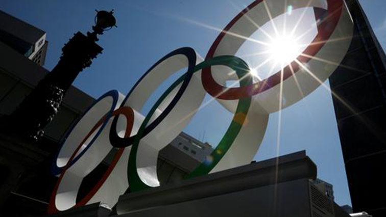 Summer sunshine is seen through Olympic rings displayed at Nihonbashi district in Tokyo.