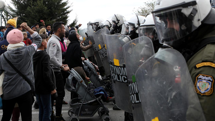 Refugees and migrants confront riot police