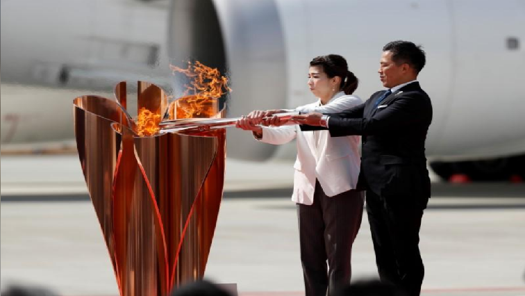 Three-time Olympic gold medalists Tadahiro Nomura and Saori Yoshida light the Olympic Flame