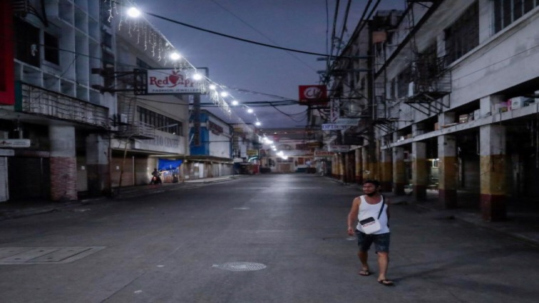 [File Image] A man wearing a protective mask on his neck walks past closed shops in an empty street following the lockdown in the Philippine capital to prevent the spread of the coronavirus disease (COVID-19), in Manila, Philippines.