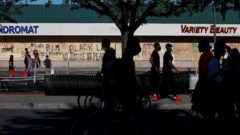 People walk past boarded up stores as demonstrations against the death in Minneapolis police custody of George Floyd continue, in Minneapolis, Minnesota, U.S.